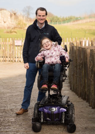 Giles Donald with a young girl using a Wheefreedom powerchair